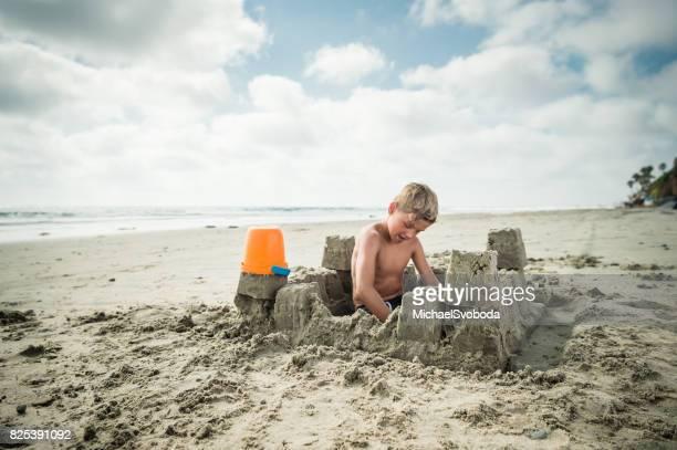 Garçon blond à la plage, construire un château de sable