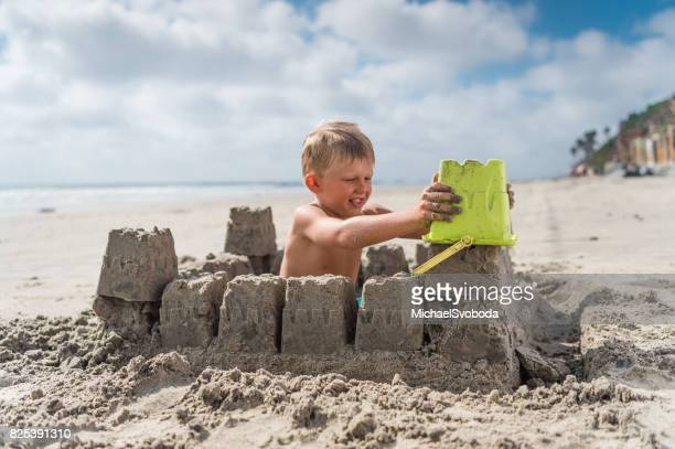 Blonde Boy At The Beach Building A Sand Castle
