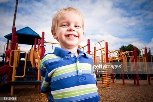 Blond petit garçon s'amusant à un terrain de jeu