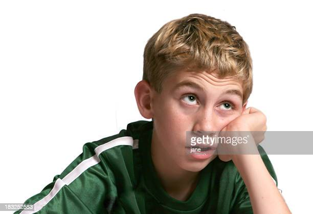 Blonde boy in green shirt staring up with bored expression