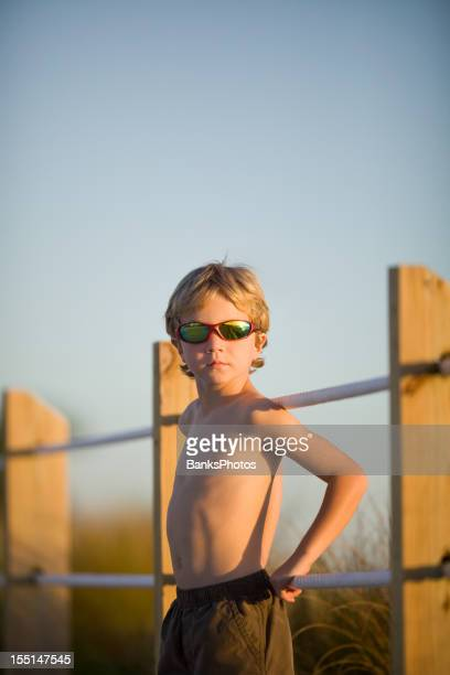 Blonde Boy Leaning Against Rope Fence at Sunset