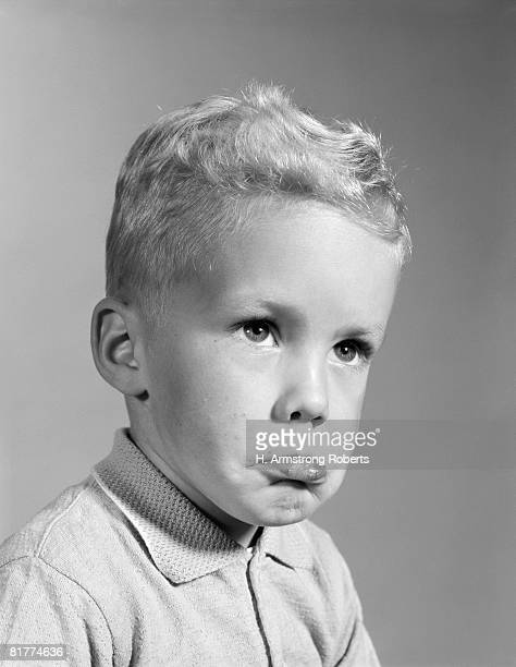 Blonde boy pouting, sticking out his lower lip, ready to cry.