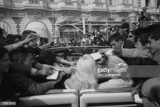 Blonde British actress Diana Dors is besieged by autograph hunters outside the Carlton Hotel during the Cannes Film Festival 3rd May 1956 Original...