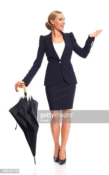 Blonde Geschäftsfrau hält Regenschirm
