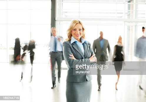 Blonde businesswoman  standing in the lobby with arms crossed.