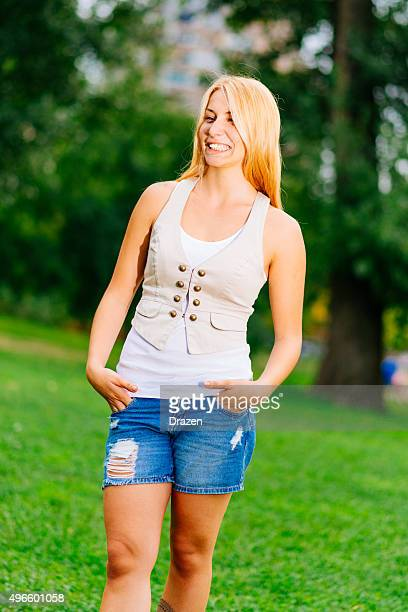 Blonde casual blonde girl smiling in park in jeans shorts
