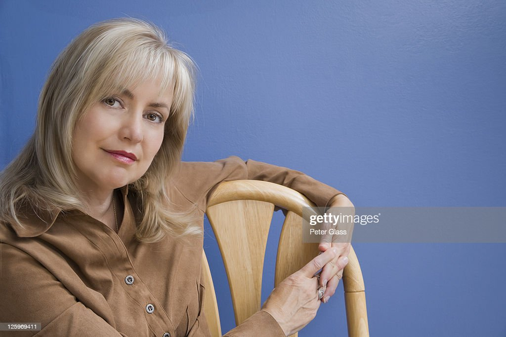 Blonde Caucasian female (52 years old) against a blue background