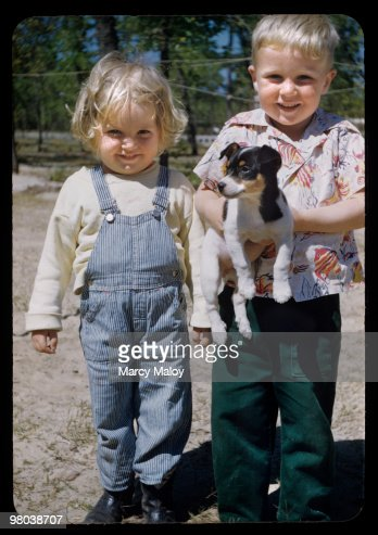 Blonde chubby toddlers hold puppy : Stock Photo