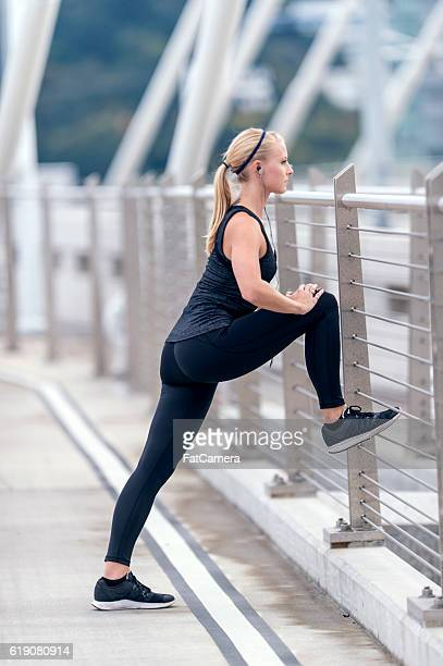 Blonde female athlete stretching in workout attire before her run