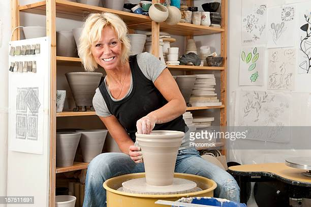 Blonde female potter sits at the pottery wheel