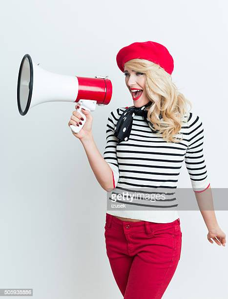 Blonde french woman wearing red beret shouting into megaphone