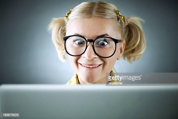 Blonde geek Blick auf Ihrem Laptop.
