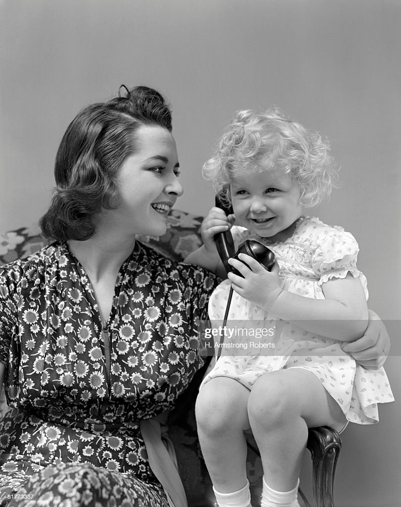 Blonde Girl Child Talking On Telphone Smiling Sitting Next To Mother With Sunflower Print Dress Smiling. : Stock Photo