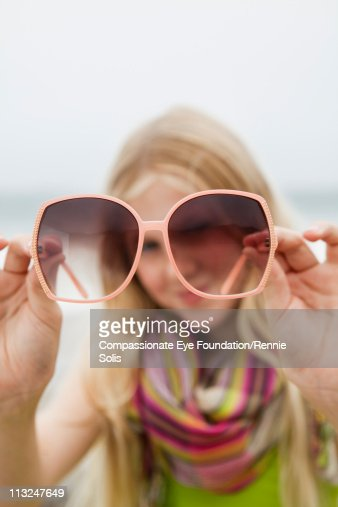 Blonde girl holding and looking through sunglasses : Stock Photo