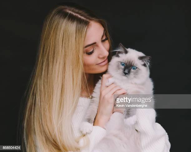 blonde girl holding her ragdoll kitten