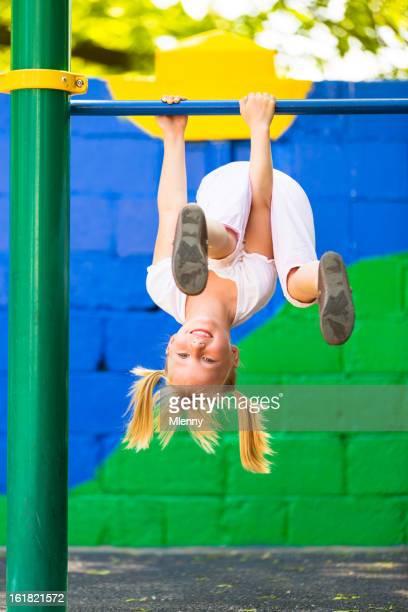 Blonde girl playing on playground gymnastics bar