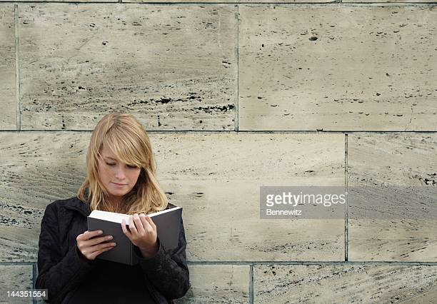 Blonde girl reading a book leaning against a stone wall