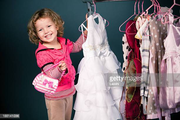 Blonde girl shopping for dresses while carrying little purse