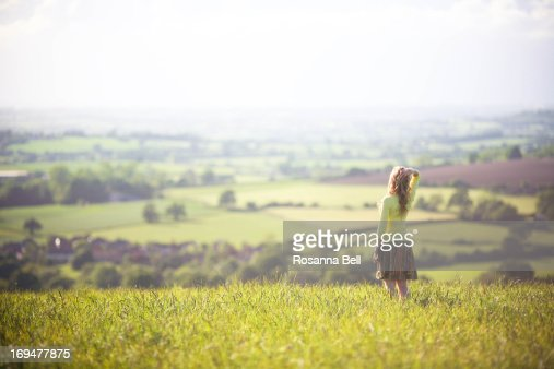 Blonde girl standing in a field admiring the view