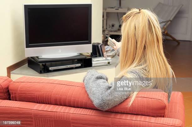 Biondo ragazza guardando la TV su un divano