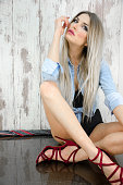 Blonde girl with a denim jacket and underwear sitting on the floor and posing