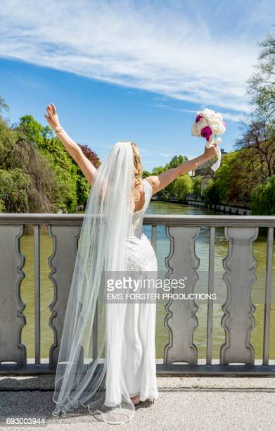 blonde haired bride seen from behind wearing her white wedding dress with train while holding her bridal bouquet of flowers consisting of white and pink peony flowers in her right hand up in the air  - she stands on a Isar bridge in Munich on a sunny day