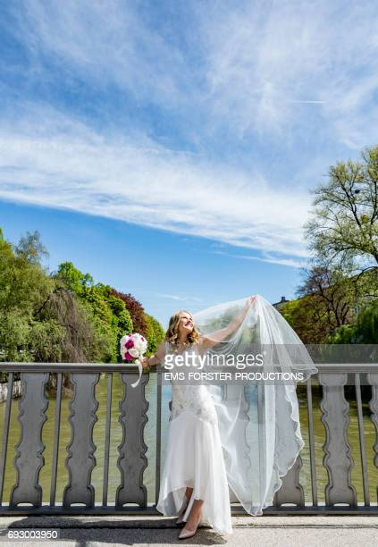 blonde haired bride wearing her white wedding dress holding up her train in the air while holding her bridal bouquet of flowers consisting of white and pink peonies in her right hand  - leaning on a Isar bridge in Munich on a sunny day