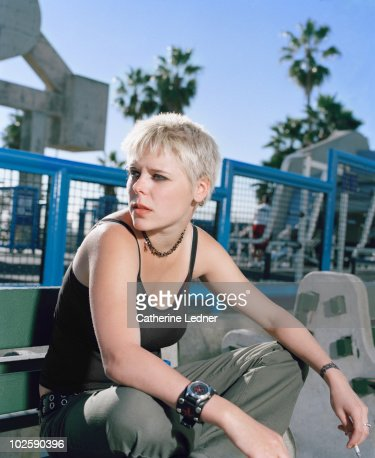 Blonde Haired Girl Sitting and Smoking : Stock Photo
