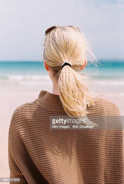 A blonde haired woman looking out to sea from the shore.