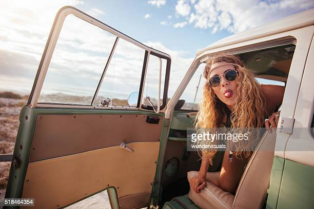 Blonde Hipster Girl Sticking Her Tongue Out on road trip