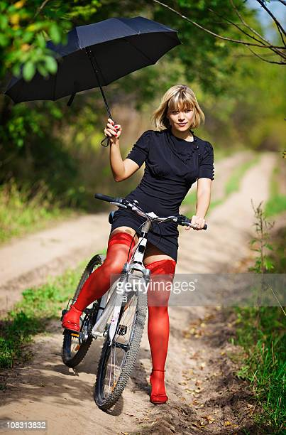 Blonde in red stockings on a bicycle with an umbrella