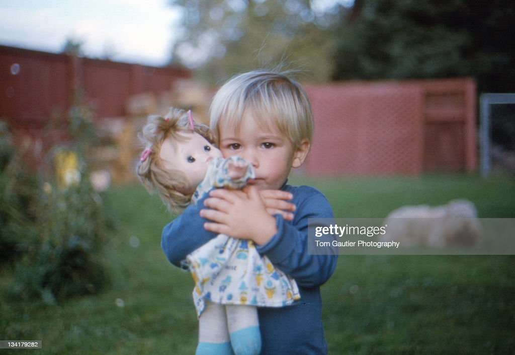Blonde infant boy hugging sisters doll