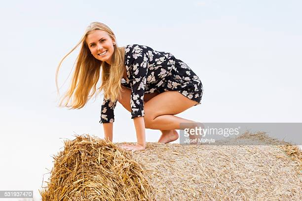 Blonde jumps from straw bale down