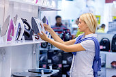 Woman shopping iron in electronics store