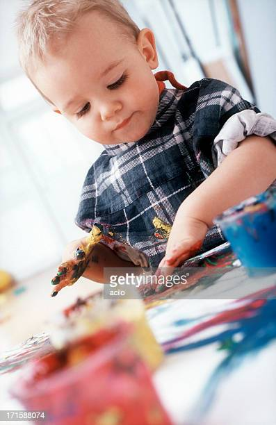 Blonde little boy is busy painting with his fingers