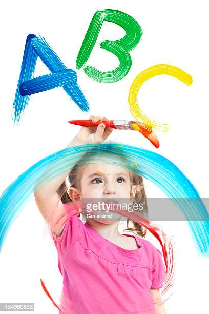 Blonde little girl painting ABC on different layers of windows