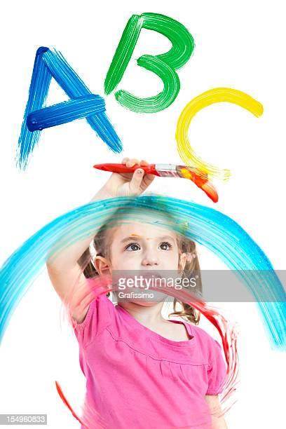 Blonde petite fille peinture ABC sur différentes couches de fenêtres