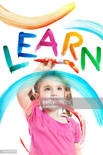 Blonde little girl painting the word learn on window