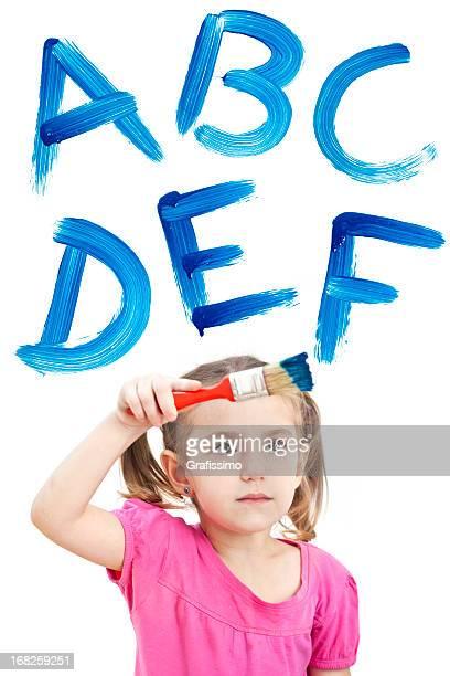 Blonde petite fille peinture Bleu ABC sur la fenêtre avec