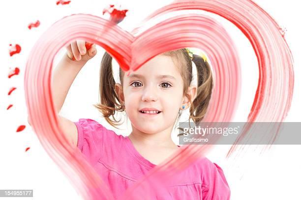 Blonde petite fille peinture de couleur coeur sur la fenêtre