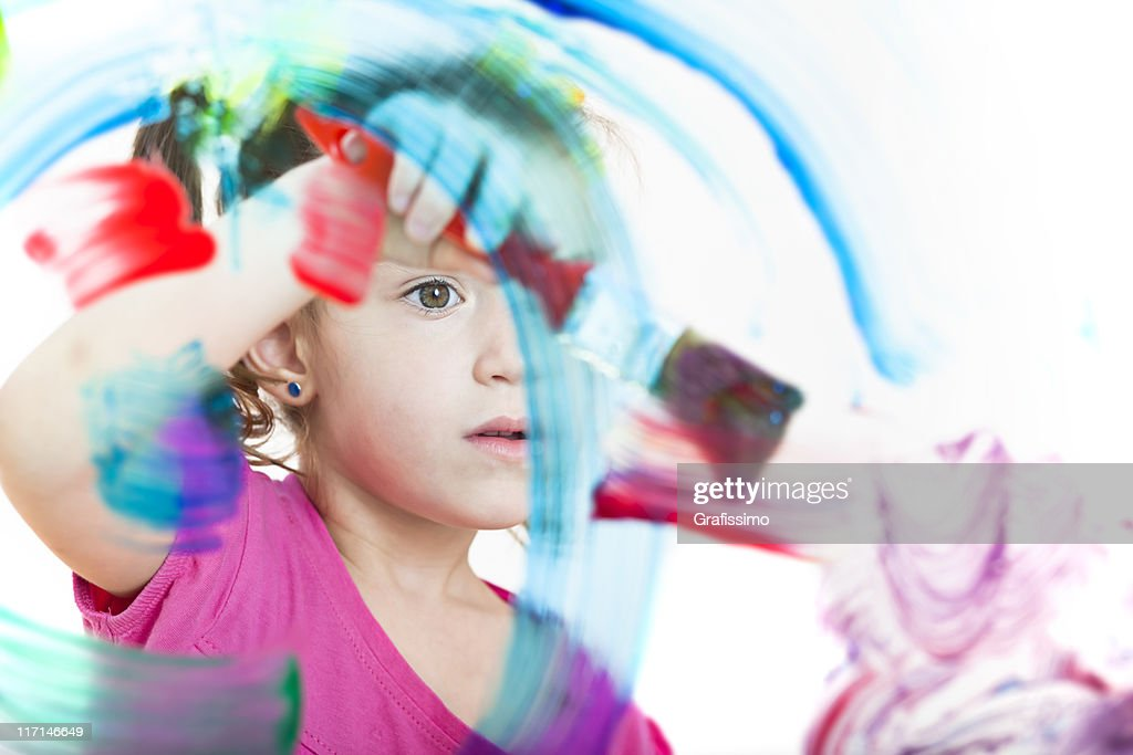 Blonde little girl painting with colours on window : Stock Photo