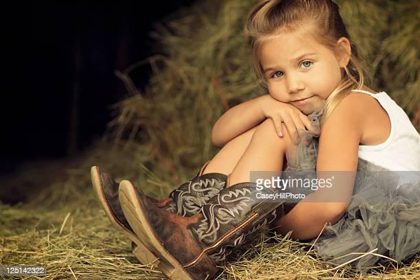 Blonde little girl sitting in hay
