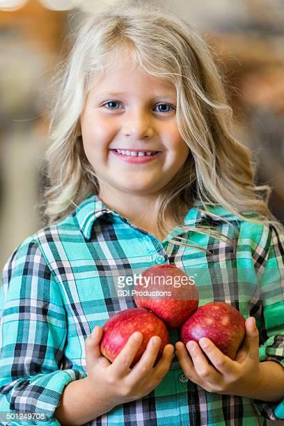Blonde kleine Mädchen Lächeln und hält Äpfel in Lebensmittelgeschäft
