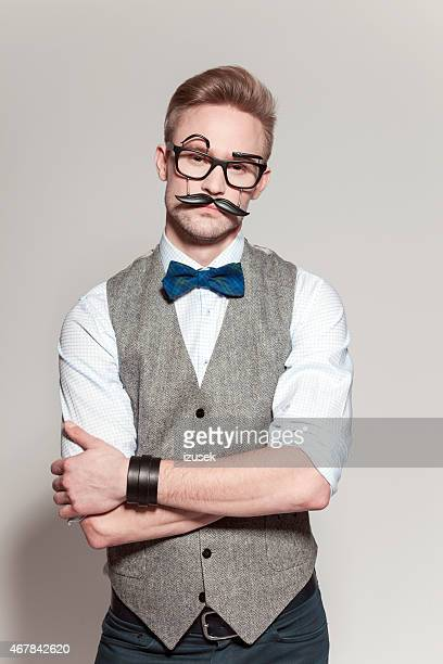 Blonde man wearing tweed vest, bow tie and funny glasses