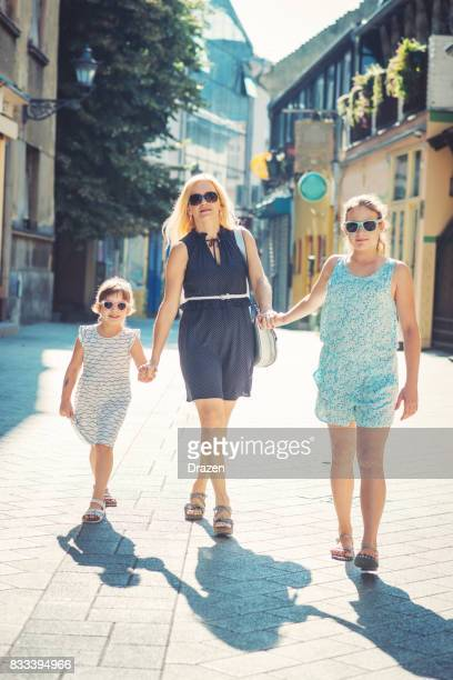 Blonde mother with young daughters walking in downtown