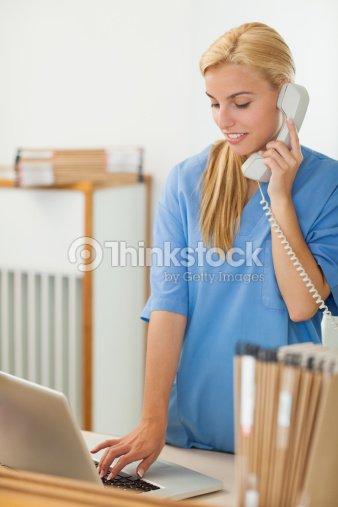blonde nurse calling while using a laptop stock photo thinkstock