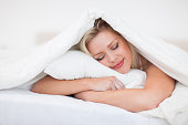 Blonde resting while embracing her pillow in a bed