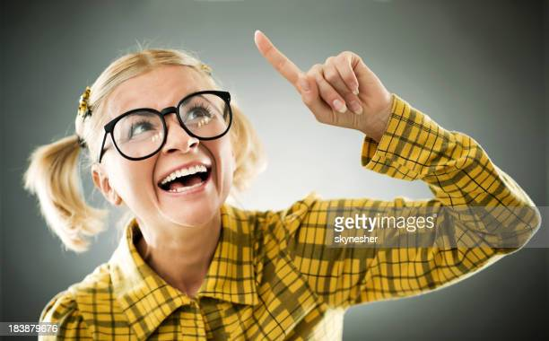 Blonde smiling nerd pointing with her finger.
