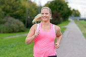 Front view of blonde smiling woman wearing sportswear running along river, close up.
