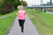 Front view of blonde smiling woman wearing sportswear running along river